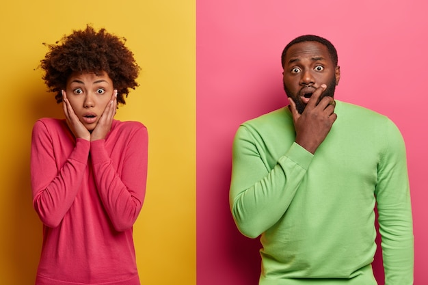 Photo of startled emotional ethnic woman and man terrified by shocking news, cannot believe their eyes, pose against bright pink and yellow wall. people and emotions concept