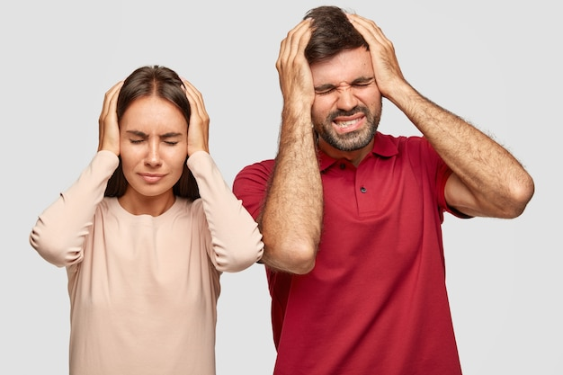 Photo of stressful depressed woman and man have terrible headache as work day and night, have deadline