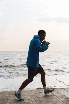 Photo of a strong handsome young african sports man boxer outdoors at the beach sea walking make boxing exercises.