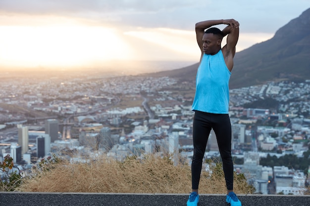 Photo of strong man with good flexibility raises hands above head, does sport exercises in open air at hill against panoramic view with sunrise, town buidling and rocks. athletic black guy has workout