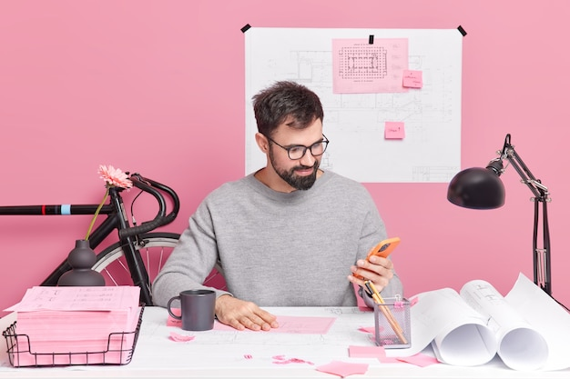 Photo of student engineer does homework makes drawings checks email box via smartphone wears spectacles and jumper poses in coworking space prepares architectural project sits at office desk