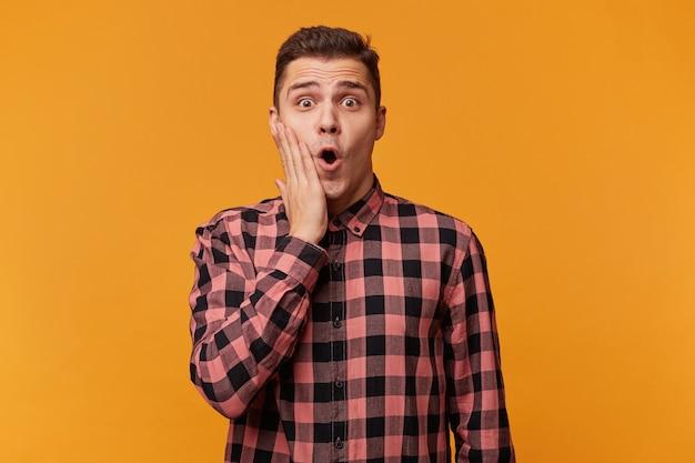 La foto di un ragazzo attraente sbalordito appare con un'espressione inaspettata direttamente sul davanti, scioccato nel ricevere notizie indecifrabili