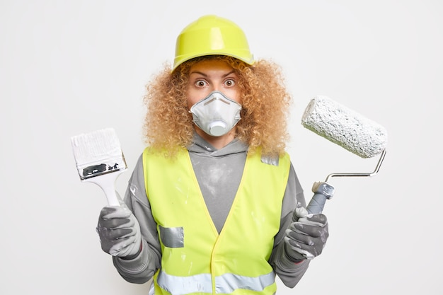 Photo of stunned curly female engineer holds painting roller and brush going to redecorate house dressed in building uniform paints interior wall of new apartment