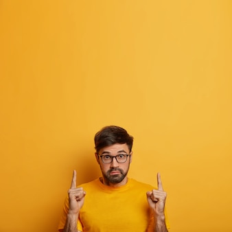 Photo of stunned man shows product, recommends service with amazed expression, stares with bugged eyes, indicates on blank space upwards, wears optical glasses, isolated on yellow wall
