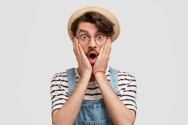 Photo of stunned young bearded male farmer keeps both palms on cheeks, hears bad news about situation on farm, dressed in white striped t-shirt and denim overllas, isolated over white wall