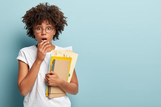 Foto di uno studente afroamericano stupito che sta per fare corsi extra, sussulta per la sorpresa, tiene la mano sulle labbra