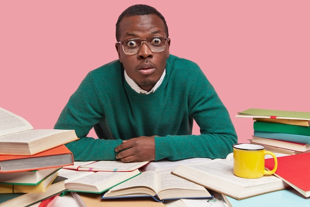 Photo of stupefied dark skinned man stares with widely opened eyes, dressed in green sweater, surrounded with much literature, writes course paper