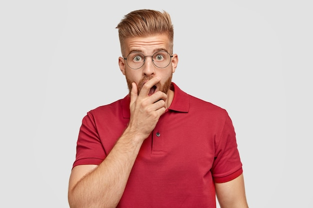 Photo of stupefied ginger hipster covers mouth with hand, afraids of something