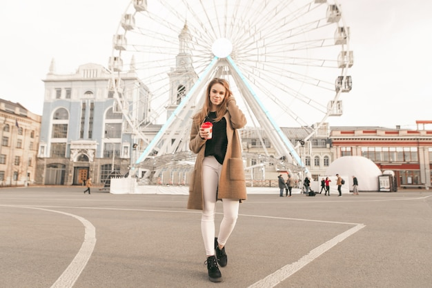 Photo of a stylish girl at full height, walking along the street with a cup of coffee in her hand, wearing a coat, looking into the camera and correcting her hair