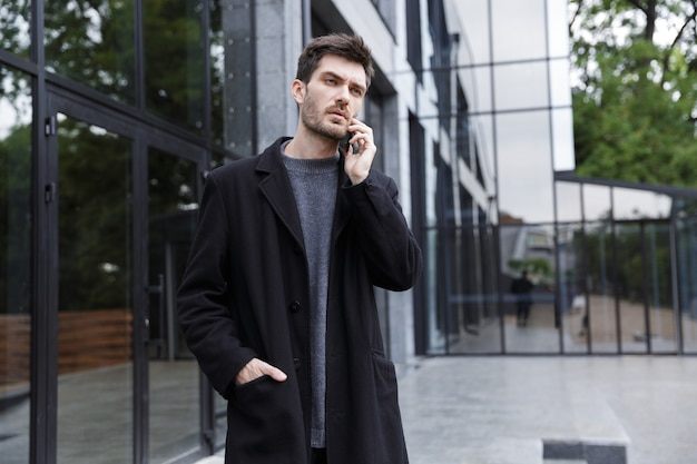 Photo of stylish man 20s talking on cell phone, while walking outdoor near glass building