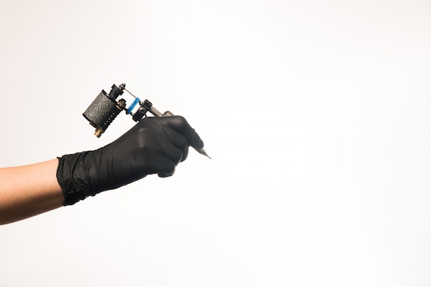 Photo of stylish tattoo machine in hand