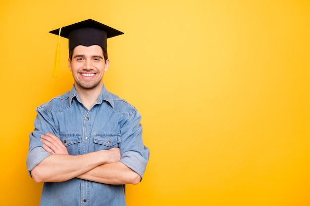 Photo of stylish trendy cheerful confident man with hands folded smiling toothily in mortarboard isolated vivid color wall