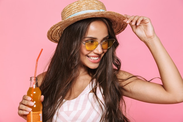 Photo of stylish woman 20s wearing sunglasses and straw hat drinking juice from glass bottle, isolated over pink wall
