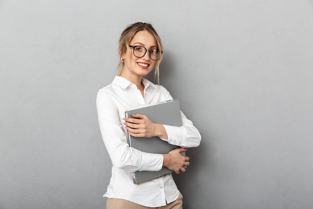 Photo of successful businesswoman wearing glasses holding paper folders in the office, isolated