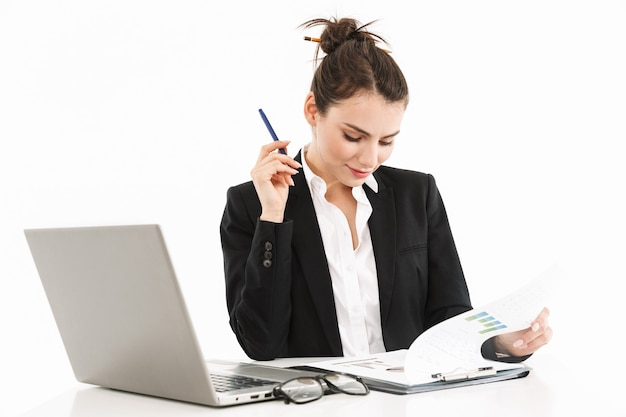 Photo of successful female worker businesswoman dressed in formal wear sitting at desk and working on laptop in office isolated over white wall