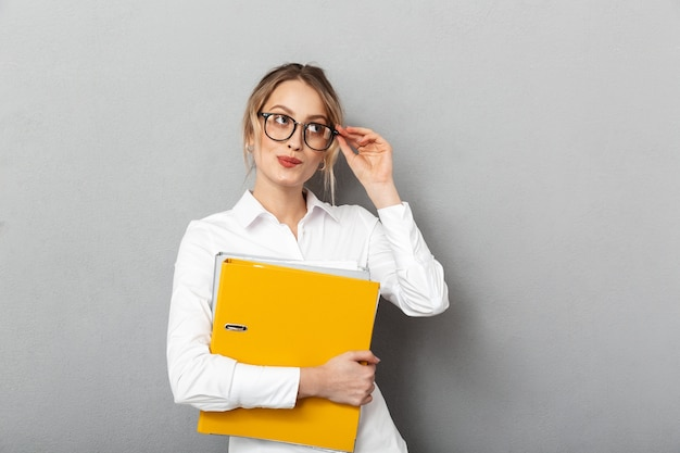 Photo of successful secretary wearing glasses holding paper folders in the office, isolated