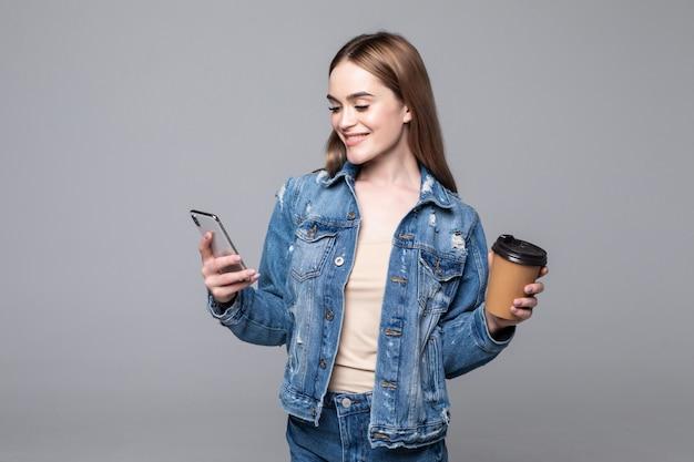 Foto di riuscita donna che sta con lo smartphone e il caffè asportabile in mani isolate sopra la parete grigia