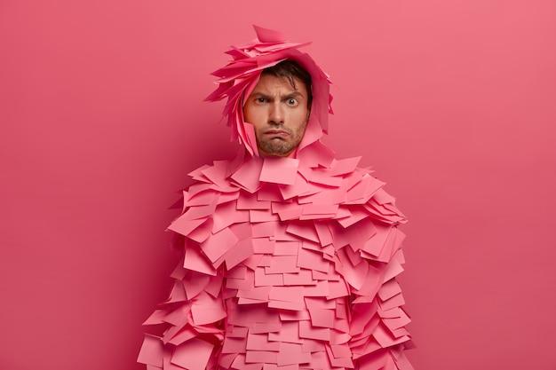 La foto di un uomo europeo scontroso e dispiaciuto solleva le sopracciglia, ha un'espressione cupa, fa una smorfia infelice, indossa adesivi rosei in giro, scontento per qualcosa, isolato su un muro rosa