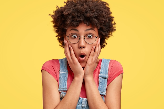Photo of surprised african american female touches cheeks, opens eyes and mouth widely, dressed in casual clothes, isolated over yellow wall. shocked mixed race woman poses alone indoor.
