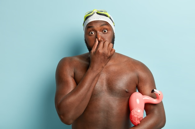 Photo of surprised african american man covers nose, has bated breath before diving, carries swimming ring under arm