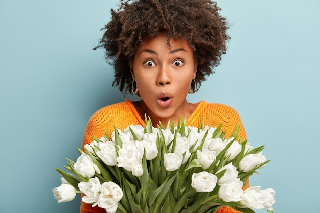 Photo of surprised african american woman with bated breath, can not believe eyes she received such big bunch of spring flowers, opens mouth from shock, isolated over blue wall. wow, what tulips