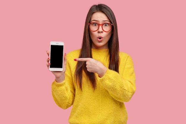 La foto della donna attraente sorpresa indica lo schermo vuoto vuoto del gadget moderno, mantiene la mascella aperta, indossa abiti gialli
