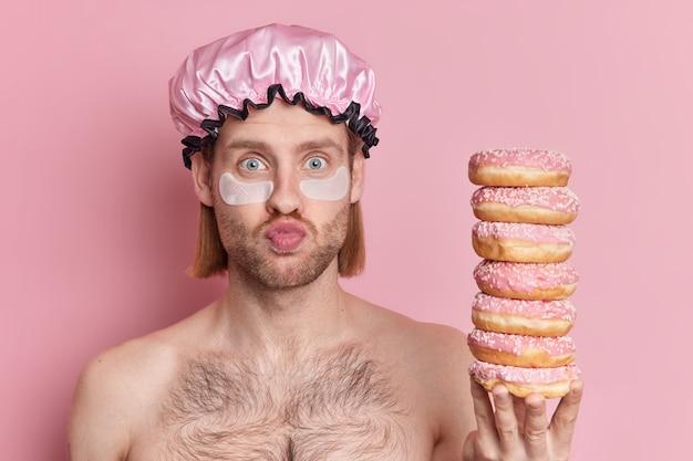 La foto di un uomo adulto barbuto sorpreso tiene le labbra piegate tiene un mucchio di ciambelle indossa cappello da bagno e toppe di bellezza per ridurre le rughe sta a torso nudo