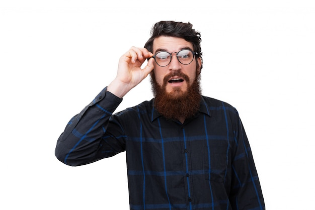 Photo of surprised bearded man, touching his glasses
