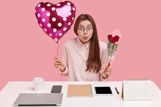La foto della giovane e bella donna sorpresa tiene le labbra rotonde, trasporta palloncini e rose, guarda attraverso gli occhiali