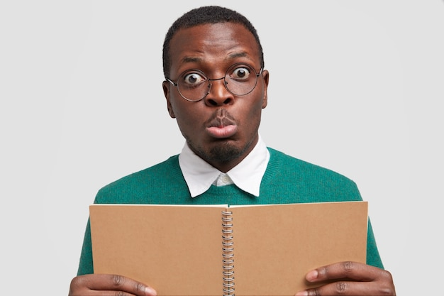 Photo of surprised black emotional young man purses lips, has eyes full of shock, holds spiral notepad, cramms material for examination session