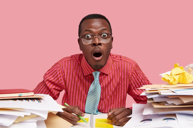 Photo of surprised black ethnic man dressed in formal elegant shirt with tie, surprised with ideas and information, works on startup project, holds pen