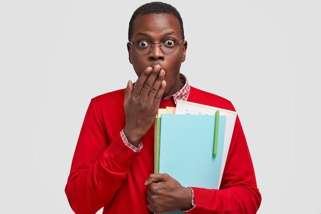 La foto dell'uomo nero sorpreso copre la bocca con il palmo, ha un'espressione spaventata, trasporta libri di testo, vestito con un maglione rosso e occhiali
