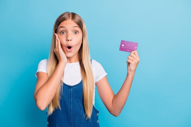 Photo of surprised cheerful blond hair teen girl hold bank card wear casual outfit isolated on pastel blue color background