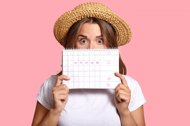 Photo of surprised dark haired woman hides behind periods calendar, wears casual white t shirt and straw hat, shocked with date of ovulation, isolated on pink, controls menstruation