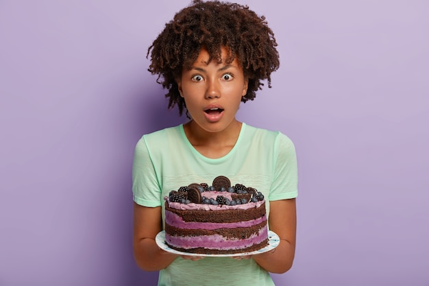 Photo of surprised dark skinned woman with curly haircut, holds delicious cake, surprised guests ate already on threshold, dressed in casual wear, baked tasty dessert