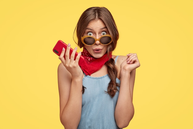 Photo of surprised emotive dark haired woman in trendy shades holds cell phone, hears something astonishing, wears red bandana, models over yellow wall. people, reaction and style concept.