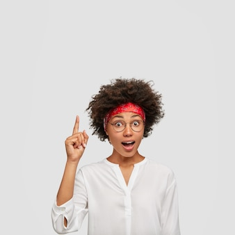 Photo of surprised ethnic lady with stunned expression, points with index finger upwards, gets interesting idea