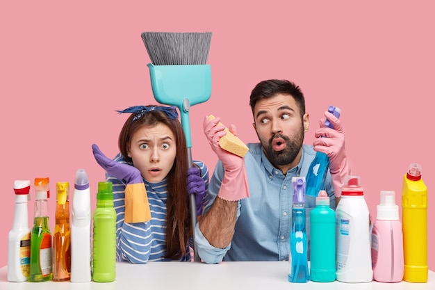 Photo of surprised european lady looks with bewilderment, astonished bearded man carries sponge and cleanser