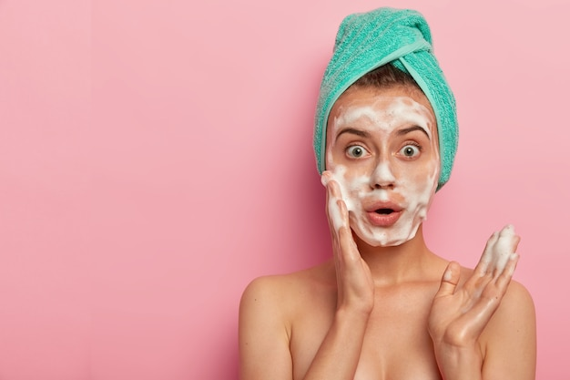 Photo of surprised european woman washes face with foam gel, wants to have refreshed well cared skin, stands topless, wears wrapped towel on wet hair, poses against pink background, free space aside