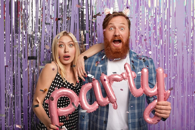 La foto della ragazza e del ragazzo sorpresi ha espressioni stupite, tiene palloncini a forma di lettera