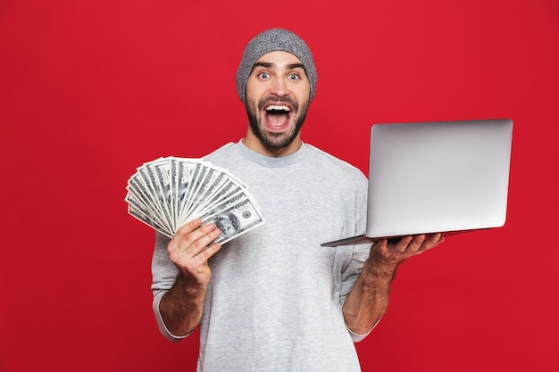 Photo of surprised guy 30s in casual wear holding cash money and silver laptop isolated
