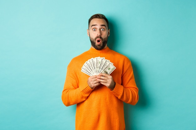 Photo of surprised guy holding money, looking amazed, standing with dollars against turquoise wall