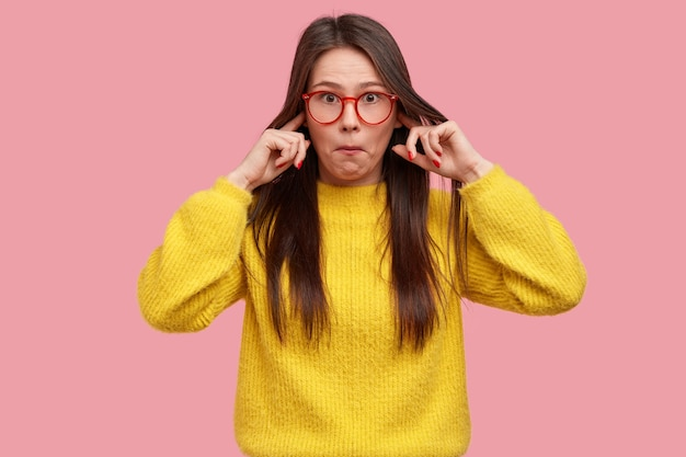 Photo of surprised lady cant stand terrible sound, surprised with rumors, pluggs ears, wears yellow clothes