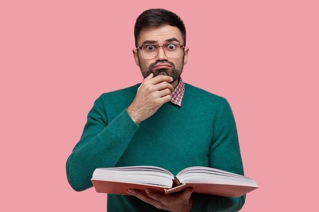 Foto di un adulto maschio sorpreso con un'espressione facciale divertente, tiene il mento, ha la barba scura, porta un libro aperto