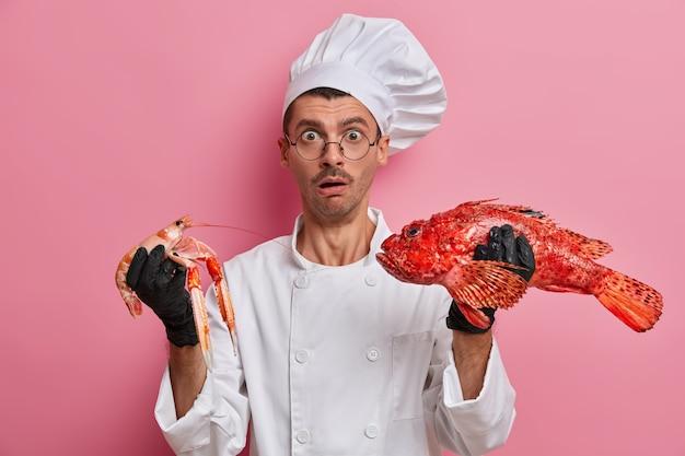 La foto del cuoco uomo sorpreso tiene crefish e branzino rosso, andando a preparare un piatto a base di pesce, prova la migliore ricetta, sta in cucina, vestito in uniforme bianca