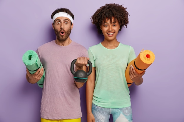 Photo of surprised man holds mat and weight, wears headband and t shirt, cheerful dark skinned woman carries fitness mat, ready for training with coach