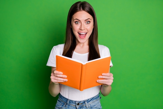 Photo of surprised pretty cheerful brunette girl read book wear white t-shirt isolated on green color background
