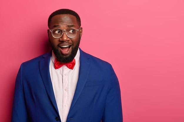 La foto di un uomo afroamericano con la barba lunga perplesso sorpreso tiene la bocca aperta, guarda con eccitazione da qualche parte, indossa un abito formale con papillon rosso