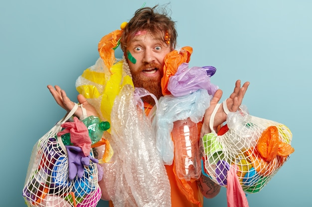 Photo of surprised red haired man has thick beard, overloaded with much garbage, collects plastic