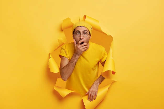 Photo of surprised scared man breaks through color paper wall, covers mouth, has stupefied expression